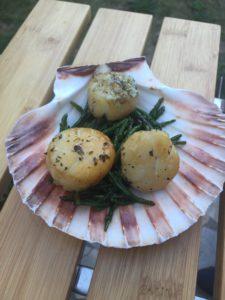 Sint Jacobsvruchten op cederplank met gebakken zeewier in boter, geserveerd op een sint jacobsschelp